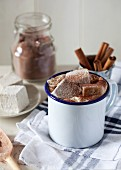 A mug of hot chocolate with cream and gingerbread marshmallows