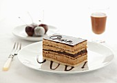 A slice of Opera Cake with cherries and a glass of chocolate liqueur in the background