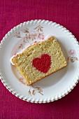 Ein Stück Biskuitkuchen mit rotem Herz zum Valentinstag
