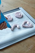 Meringue hearts being piped onto baking paper