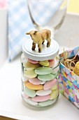 Sugared almonds for Easter in screw-top jar decorated with lamb figurine