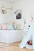 Indoor-Tipi in Pastellfarben, daneben Geweih und Bild über Kuschelplatz mit Dekokissen
