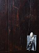 Gabeln und Löffel auf dunkelm Holzuntergrund