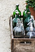 Wooden crate of empty bottles on garden path