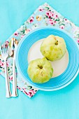 Fresh guavas on a light blue surface with floral-patterned napkins