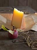 Bergkäse und angebissener Apfel auf Holzuntergrund