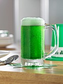 A tankard of green beer on a wooden table