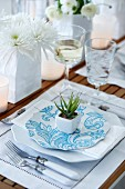 Festive place setting with a white linen place mat and a small decorative succulent plant on a plate