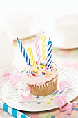 A birthday cupcake with pink frosting and five candles