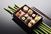 Various sushi in a rectangular tray on a mirrored table