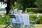 A garden table laid with a white table cloth, a wine cooler, wine glasses, a hydrangea and a fruit bowl