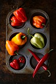 Various types of peppers in a muffin tin