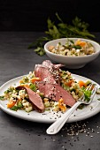 Roast lamb fillet on a bed of couscous with cucumber and dried apricots
