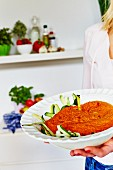 A woman carrying a bowl of detox courgette pasta with tomato sauce