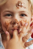 A little girl with chocolate sauce all over her face