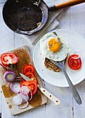 Rye bread with a fried egg, red onions and fresh tomatoes