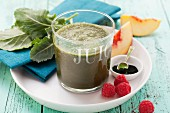 A peach smoothie made with raspberries, spinach, kohlrabi leaves and spirulina