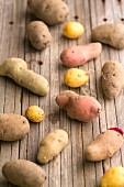 Assorted types of potato on a wooden surface