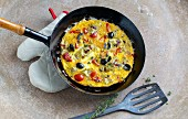 French vegetable omelette with cherry tomatoes, artichoke hearts and black olives