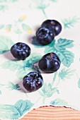 Organic blueberries on a piece of floral-patterned wallpaper