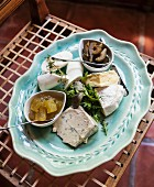 A cheese platter with herbs and pickles