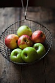 Various apples in a wire sieve