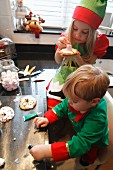 Children decorating Christmas biscuits in a kitchen