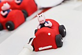 A fondant race car with a pig being finished