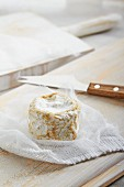 Goat's cheese on a muslin cloth with a cheese knife next to it