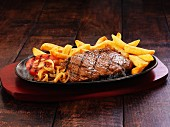 Beef steak with chips, onions and grilled tomatoes