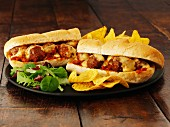 A meatball sub with cheese and crisps