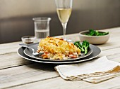 Mixed fish pie with broccoli and wine