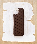 An ice cream sandwich on a piece of paper with a bite taken out