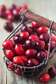 Fresh cranberries in a wire basket on a wooden surface