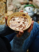 Hands holding a bowl of bicerin (chocolate and coffee drink, Turin)
