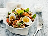 Pasta salad with hard boiled eggs, bacon, croutons and tomatoes