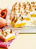 Angeschnittener Orangen-Blechkuchen mit Baiserhuabe auf einem Kuchengitter