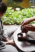 A man pouring tea for a woman in a kimono