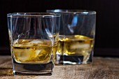 Two glasses of whisky with ice cubes