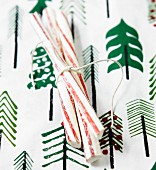 Sticks of peppermint rock on a table with a cloth decorated with Christmas trees