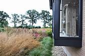 Garten mit verschiedenen Gräsern und zeitgenössisches Wohnhaus mit Erker aus Glas-Stahlkonstruktion in Grau