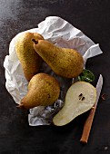 Four Abate Fetel pears on a piece of white paper with a knife