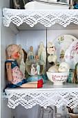 Puppe und Sammlerstücke vor Devotionalien im Regalschrank, Ablagen mit weisser Borte verziert
