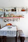 Esstisch mit Spitzedecke, antike Bank, vor Wand mit Ablagen, darauf Retro Geschirr
