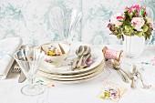 Geschirr, Besteck, Gläser, Tischkärtchen & Blumenstrauss für den österlich gedeckten Tisch