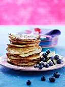 A stack of pancakes with blueberries and pear