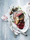 Rare grilled steaks with beetroot, mushrooms and herbal oil