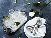Tellerstapel mit Servietten und Besteck, daneben ein Tablett mit Gläsern und eine Rose