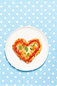 A heart-shaped mini pizza with ketchup