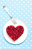 A heart-shaped cheesecake with cherry jelly